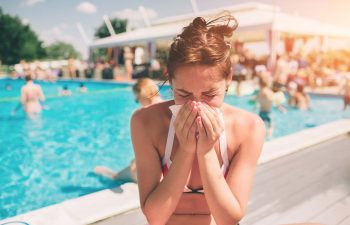 Women has runny nose in the summer on vacation.