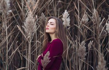 Girl with long hair wearing red shirt in forest field among large tall plants grass.